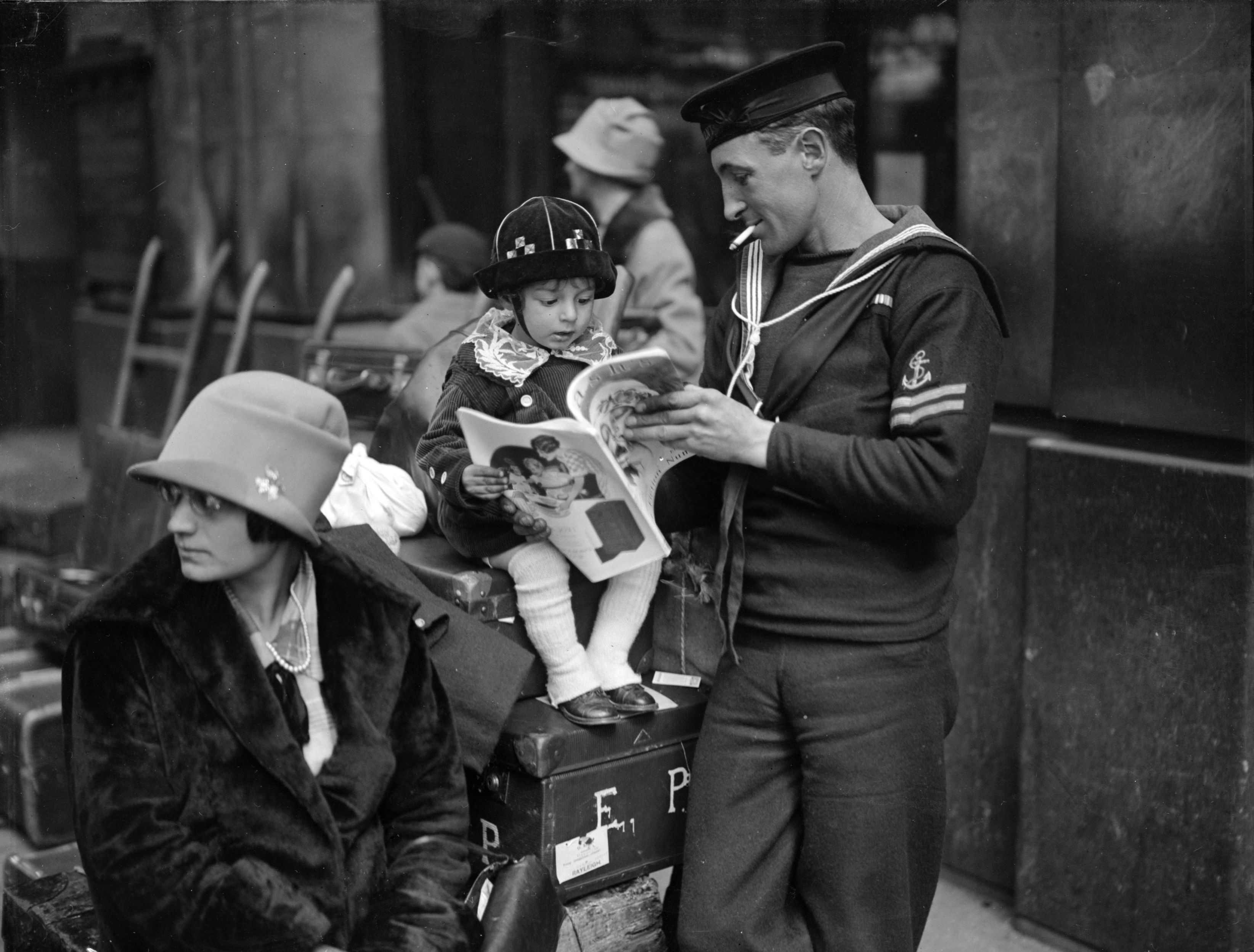 A sailor reads with his child as he waits for a holiday train at Waterloo station in London in 1927.