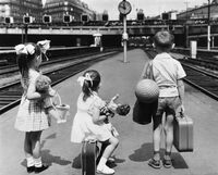 Three French children wait on a railway platform with their toys and luggage in September 1962.