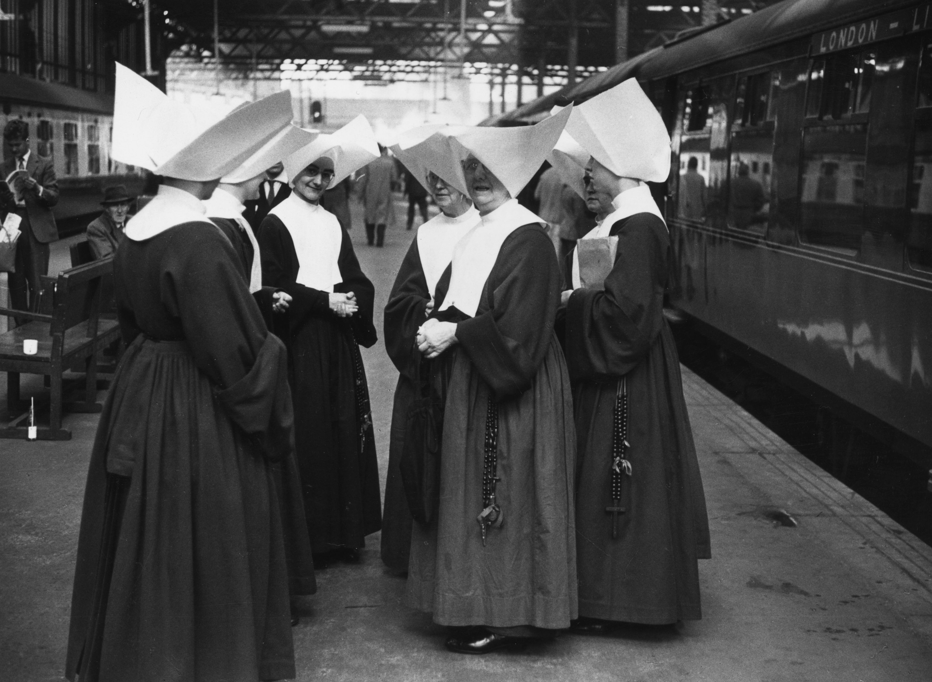 Nuns wait together on a platform at Euston station in London.