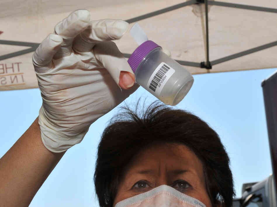 A medical worker in Carletonville, South Africa, examines a sample at a mobile testing facility for tuberculosis.