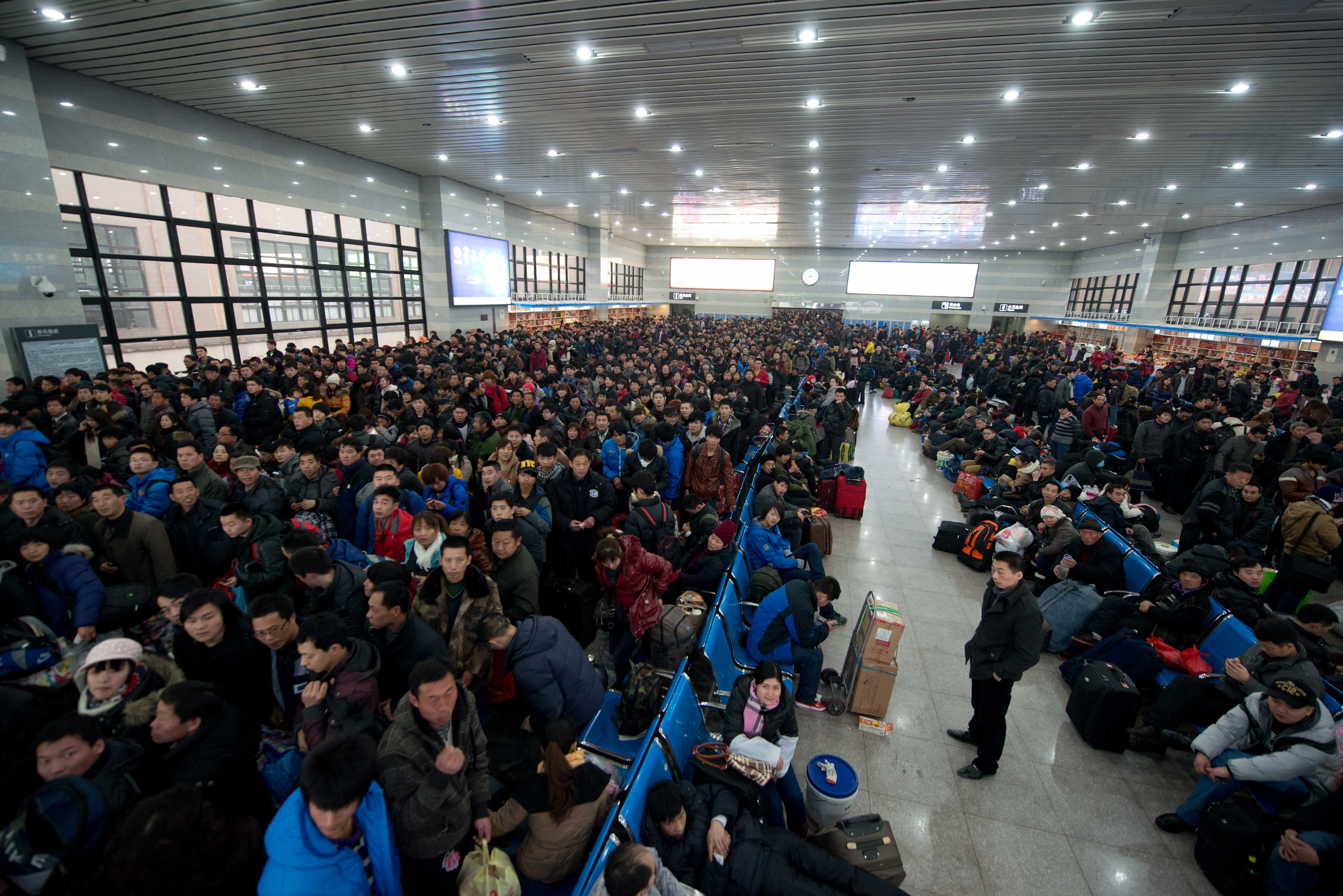 Lunar New Year travelers wait for their train at the West Railway Station in Beijing on Jan. 31, 2013. Tens of millions of people across China board trains to journey home for Lunar New Year celebrations in the world's largest annual migration.