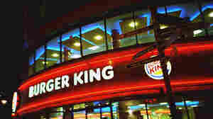 Signs point to tourist destinations outside a Burger King in London.