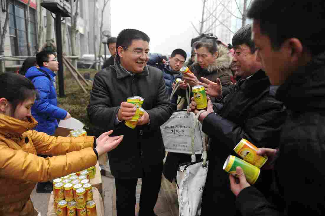 Chinese businessman Chen Guangbiao (center) gives cans of fresh air produced by his factory to passersby for free in a financial district in Beijing.
