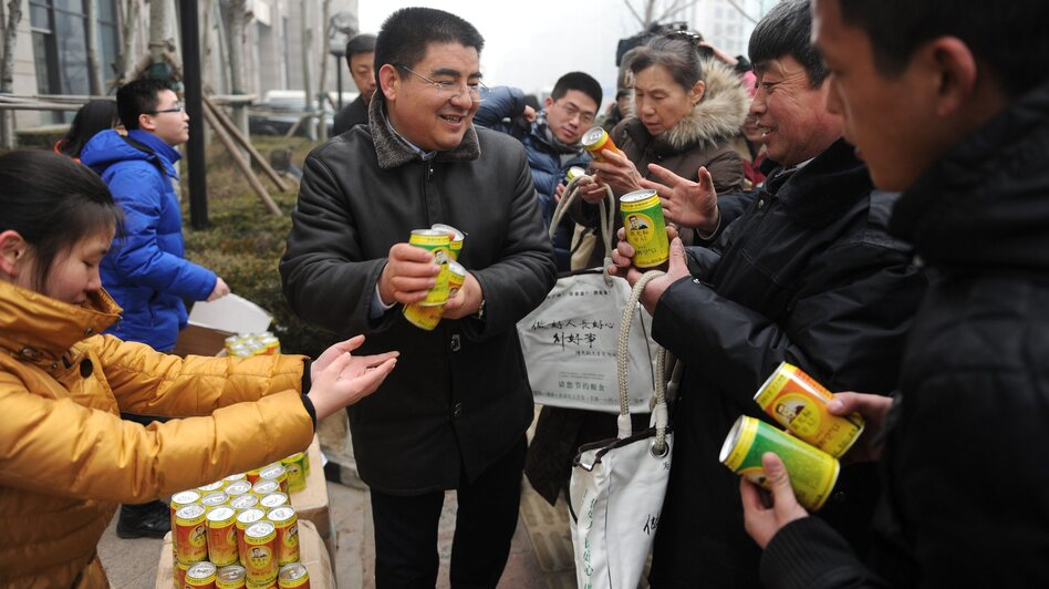 Chinese businessman Chen Guangbiao (center) gives cans of fresh air produced by his factory to passersby for free in a financial district in Beijing. (EPA /LANDOV)