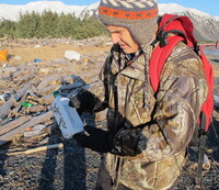 Chris Pallister examines a bottle of what he believes could be a household chemical item on Montague Island.
