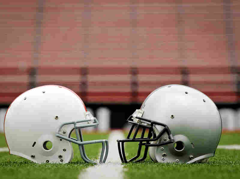 Two football helmets face each other on a field.