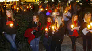 Thursday night in Midland City, Ala., there was a candlelight vigil for bus driver Charles Poland, who was killed Tuesday before a gunman snatched a 5-year-old boy — who is being held captive in an underground bunker.
