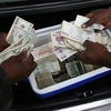 Zimbabwean foreign currency dealers conduct a transaction from the trunk of a car using money stashed in a cooler box in Harare.