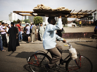 An Egyptian man delivering bread rides through Cairo's Tahrir Square last year. Couriers are taking great risks as they work around Egypt's capital.