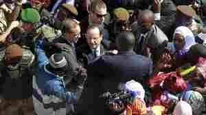 French President Francois Hollande is surrounded by well-wishers on his short visit to Timbuktu, Mali, on Saturday.
