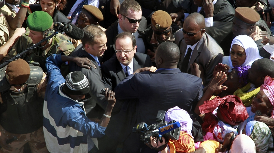 French President Francois Hollande is surrounded by well-wishers on his short visit to Timbuktu, Mali, on Saturday. (AP)