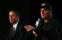 Head coach John Harbaugh (Suit-Wearing Brother) of the Baltimore Ravens and Head coach Jim Harbaugh (Hat-Wearing Brother) of the San Francisco 49ers speak to the media on Feb. 1.