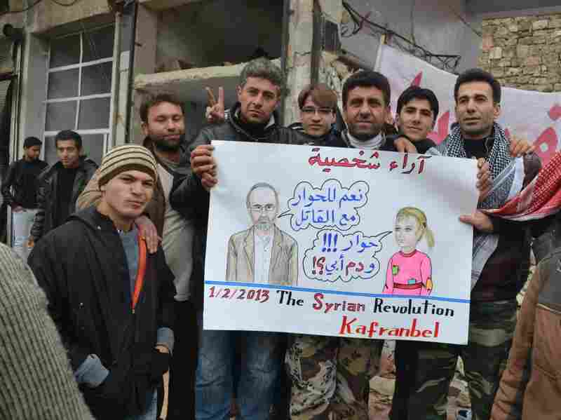 "In this poster seen in Kafr Nabl, Syria, a likeness of Syrian activist Moaz al-Khatib says: ""Yes, Dialogue with Killers,"" and a young girl asks: ""But what about the blood of my father?"""