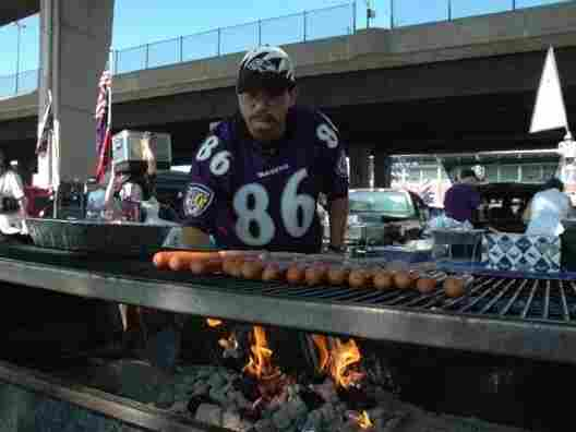 Ravens fan Michael Neapolitan at the grill after he's burned the opposing team's football cards.