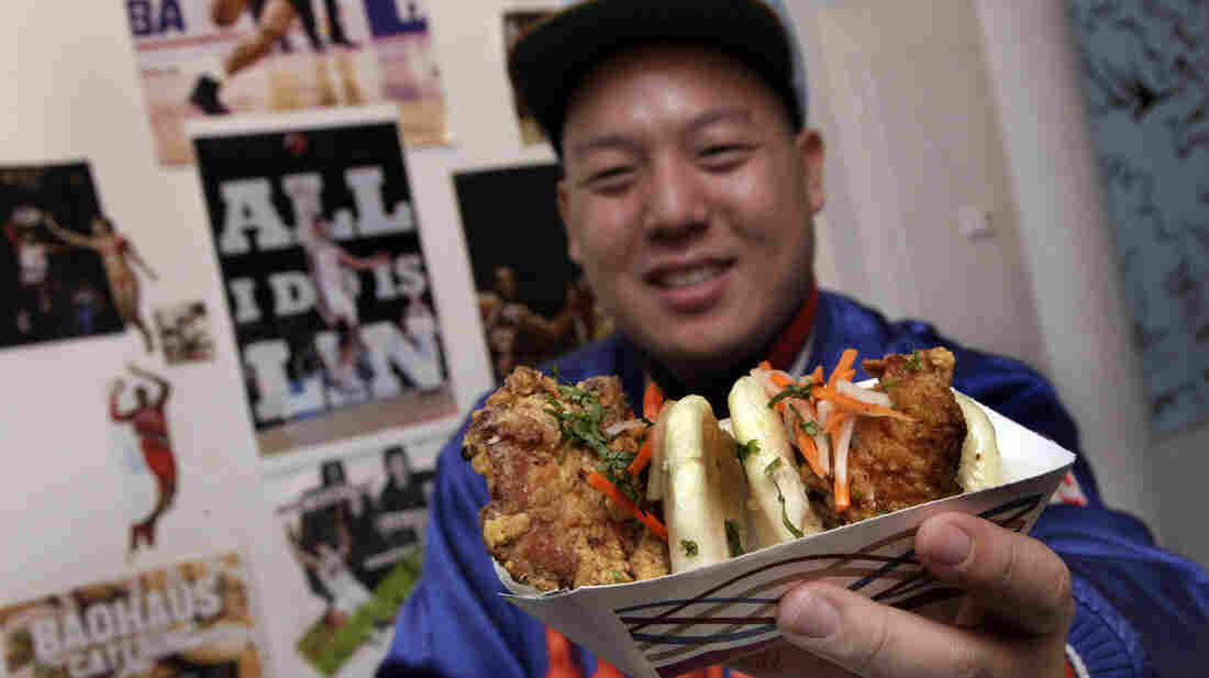 """Eddie Huang, co-owner of Baohaus and author of Fresh Off The Boat, holds a pair of """"The Taiwanese Te-Bao,"""" a Taiwanese pork chop with curry seasoning, pickles daikon-carrot, jalapeno, aioli and cilantro in a steamed bun."""