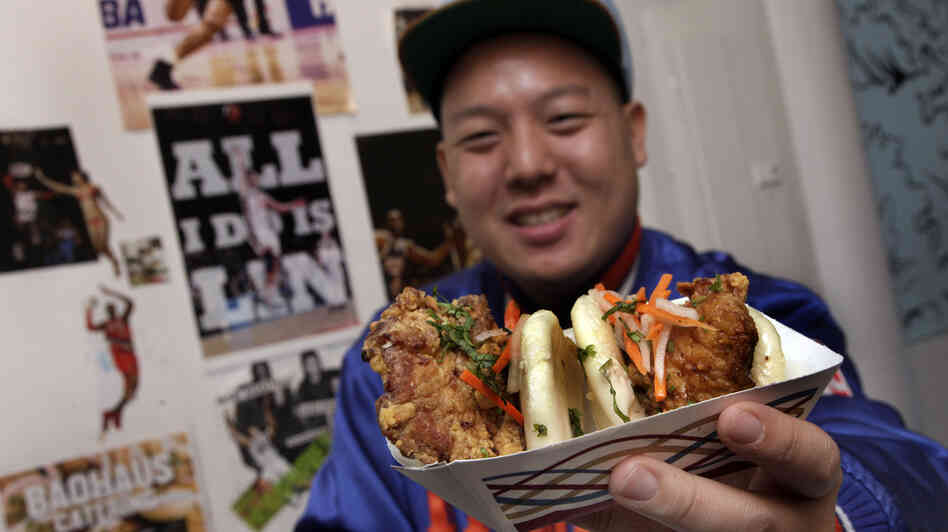 "Eddie Huang, co-owner of Baohaus and author of Fresh Off The Boat, holds a pair of ""The Taiwanese Te-Bao,"" a Taiwanese pork chop with curry seasoning, pickles daikon-carrot, jalapeno, aioli and cilantro in a steamed bun."