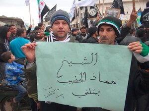 """Activists in the town of Saraqib, Syria, hold a poster that reads, """"Sheikh Moaz al Khatib represents me."""""""