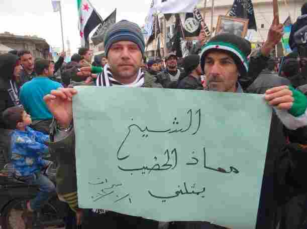"Activists in the town of Saraqib, Syria, hold a poster that reads, ""Sheikh Moaz al Khat"