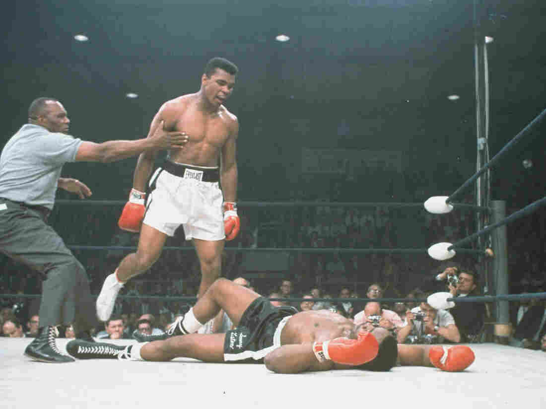 Muhammad Ali is held back by referee Joe Walcott after knocking out Sonny Liston in the first round of their championship bout in Lewiston, Maine, on May 25, 1965.