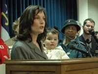 Sato holds Hana as she speaks during a 2009 press conference at the North Carolina state Legislature about the need for paid sick days.
