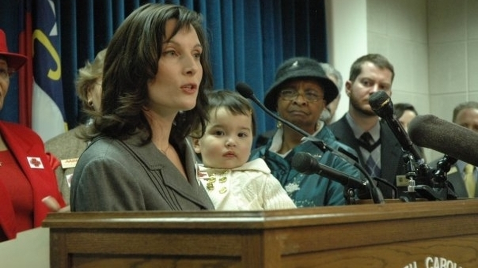 Sato holds Hana as she speaks during a 2009 press conference at the North Carolina state Legislature about the need for paid sick days. (Courtesy of Jeannine Sato )