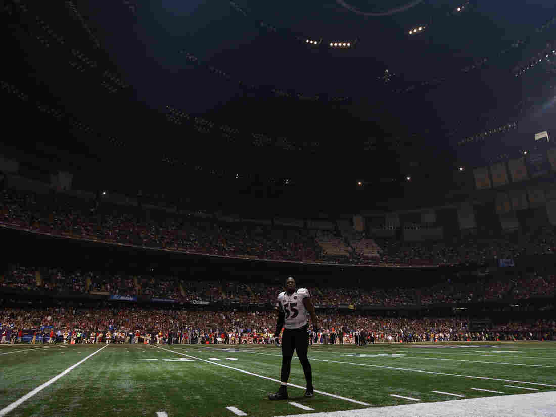 Baltimore Ravens linebacker Terrell Suggs waits on the field after the half the lights went out in the third quarter of Sunday's Super Bowl  against the San Francisco 49ers in New Orle