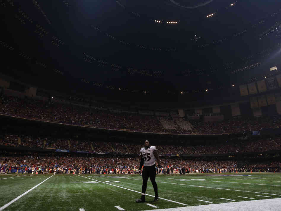 Baltimore Ravens linebacker Terrell Suggs waits on the field after the half the lights went out in the third quarter of Sunday's Super Bowl  against the San Francisco 49ers in New Orleans.