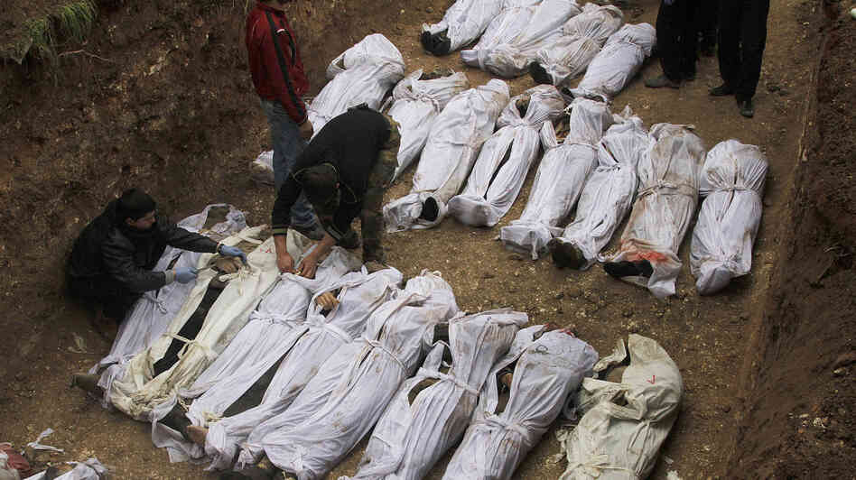 Syrian citizens bury those who were found dead next to a river last week, many of them with their hands
