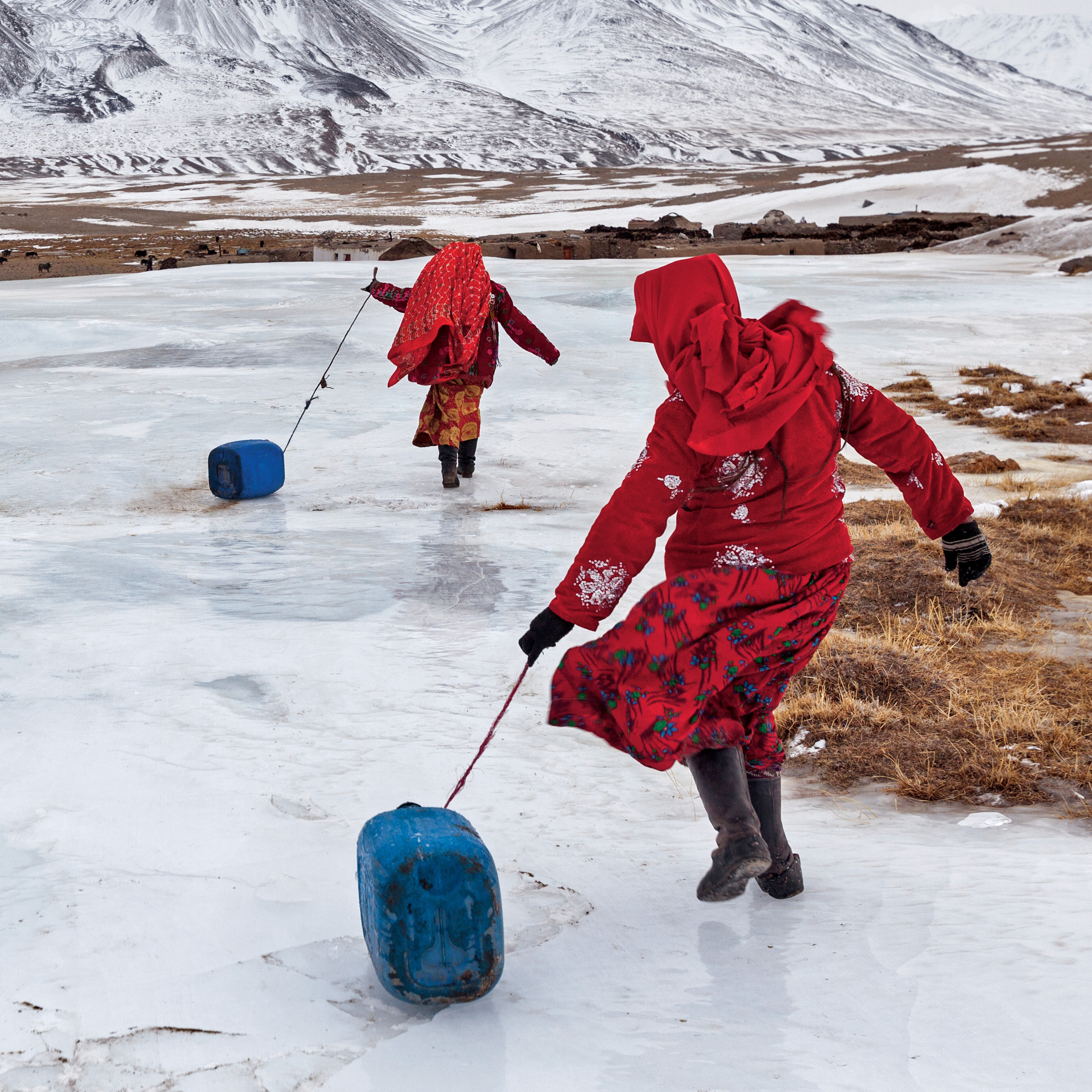 Kyrgyz girls slide plastic jugs back to their family's camp after chopping a hole in a frozen spring to fetch water. Men handle herding and trading; much of the hard labor of daily life falls to the females.