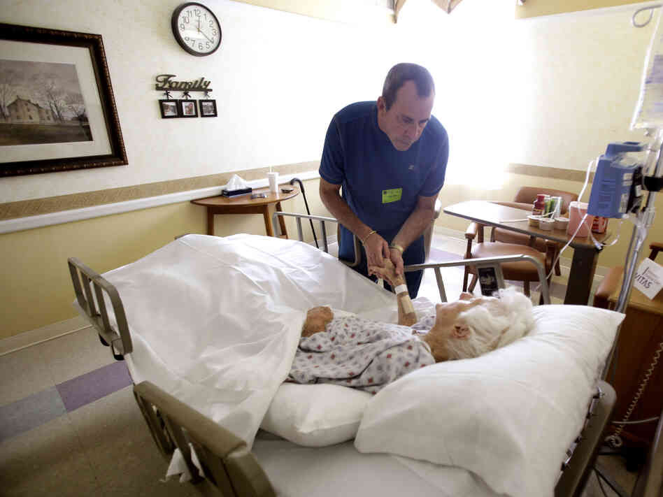Joe Takach comforts his friend Lillian Landry, as she spends her last days in the hospice wing of a hospital in Oakland Park, Fla., in 2009.