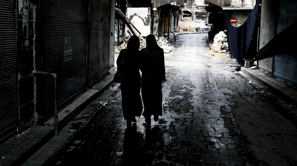 Syrian women walk through a market area in the northern city of Aleppo last November. A new website is documenting the use of rape in the Syrian conflict. (AFP/Getty Images)