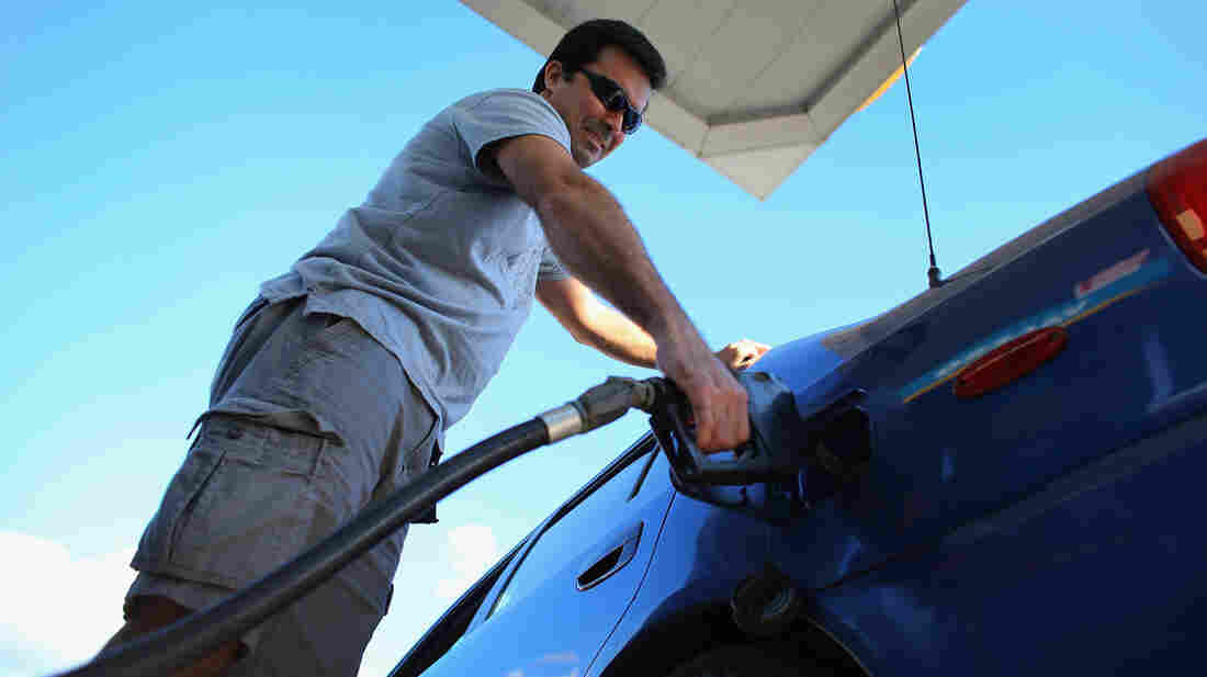 Raul Rivero fills up in Miami. Having less take-home pay at the same time gas prices are rising could dampen consumer spending, economists say.