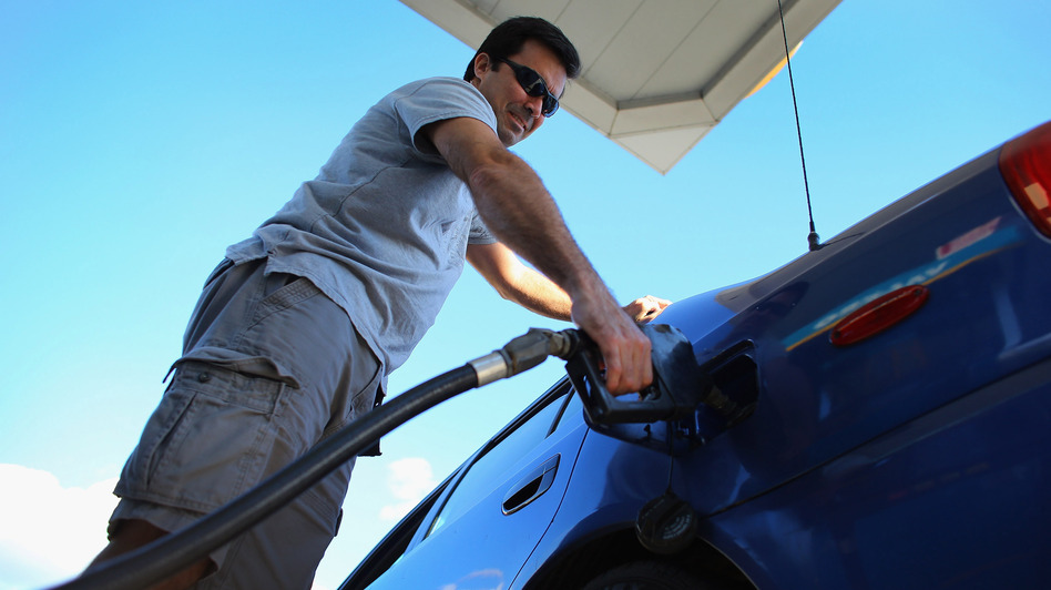 Raul Rivero fills up in Miami. Having less take-home pay at the same time gas prices are rising could dampen consumer spending, economists say. (Getty Images)