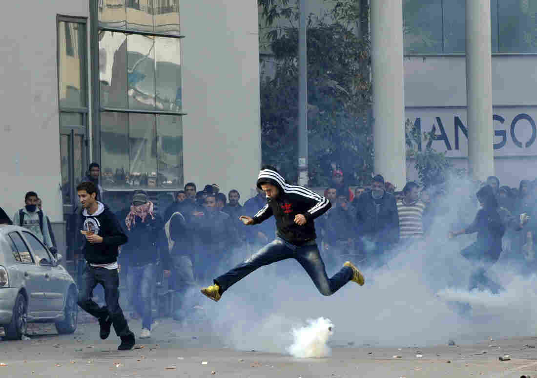 A Tunisian protester jumps amid smoke after police fired tear gas during a rally outside the Interior ministry to protest after Tunisian opposition leader and outspoken government critic Chokri Belaid was shot dead.