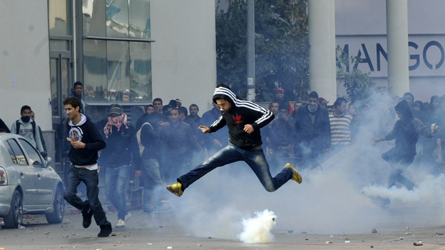 A Tunisian protester jumps amid smoke after police fired tear gas during a rally outside the Interior ministry to protest after Tunisian opposition leader and outspoken government critic Chokri Belaid was shot dead. (AFP/Getty Images)