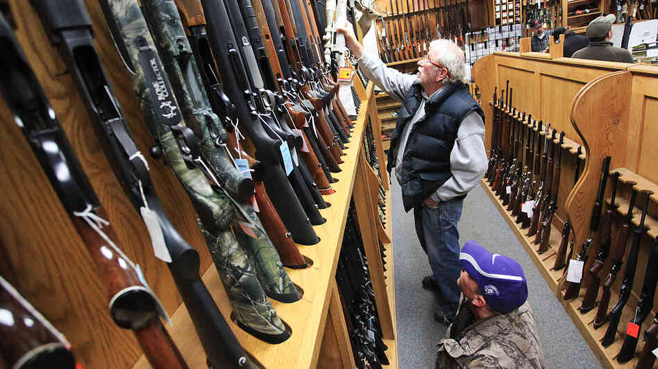 Jeff Torgerson (top) and Dan Volkman browse the selection of rifles at Mainstream Firearms and Marine in Winona, Minn.,