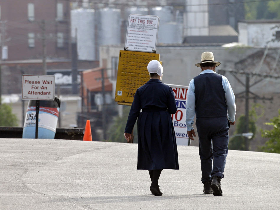 An Amish man and woman walk through a parking lot after leaving the U.S. courthouse in Cleveland in September. Sixteen members of an Amish group in Bergholz, Ohio, led by Samuel Mullet, were found guilty of attacks targeting Amish bishops.