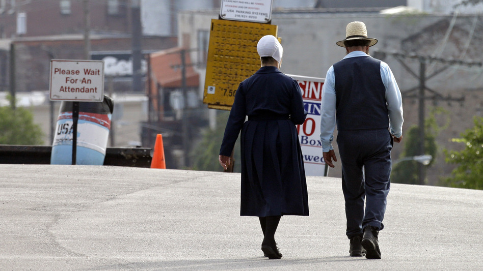 An Amish man and woman walk through a parking lot after leaving the U.S. courthouse in Cleveland in September. Sixteen members of an Amish group in Bergholz, Ohio, led by Samuel Mullet, were found guilty of attacks targeting Amish bishops. (AP)