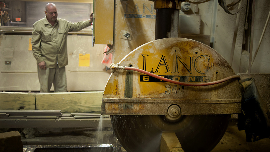 An employee uses a wet saw to cut a slab of sandstone at a Lang Stone Co. facility in Columbus, Ohio, in January. Using water while cutting helps keep dust out of the air. (Bloomberg via Getty Images)