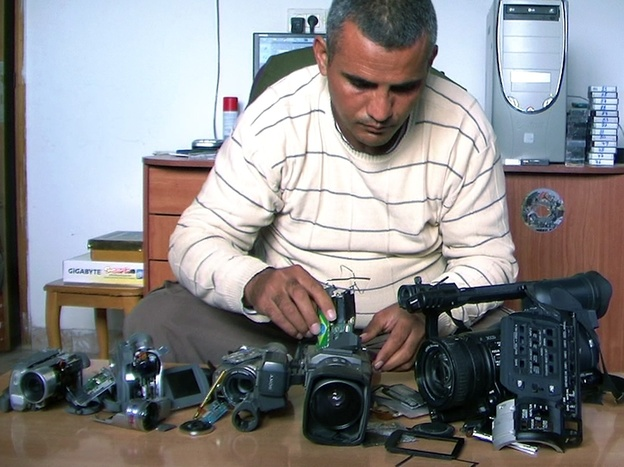Co-director Emad Burnat examines his five broken cameras. (Kino Lorber, Inc)