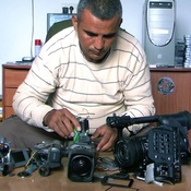 Co-director Emad Burnat examines his five broken cameras.