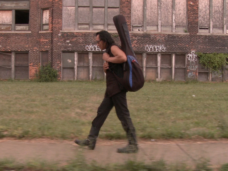 Rodriguez carries his guitar through Detroit, Mich., his hometown. (Sony Pictures Classics)