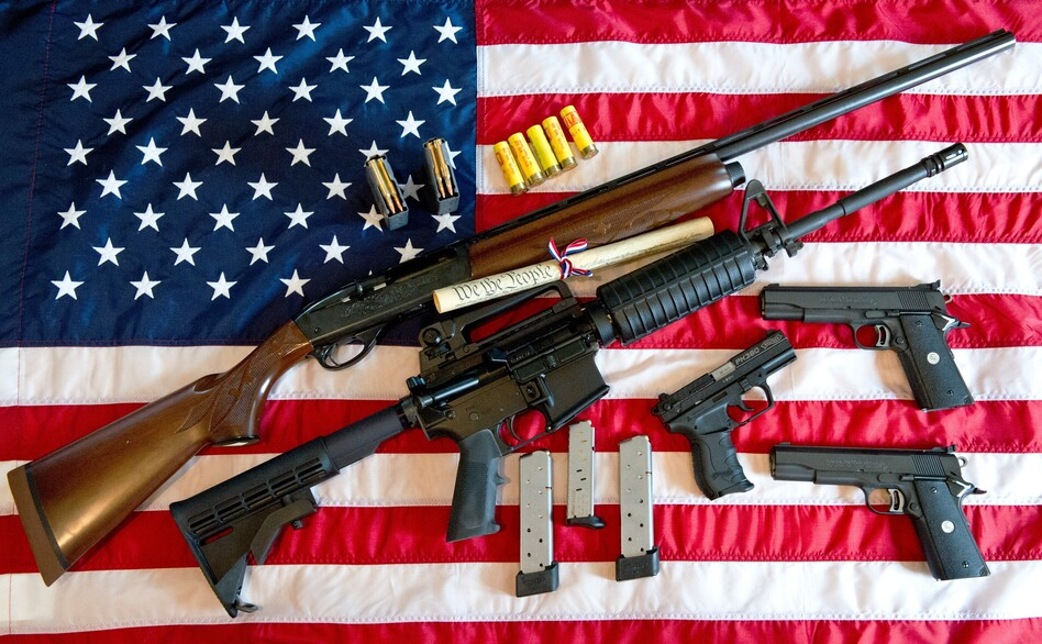 A photo illustration showing a Remington 20-gauge semi-automatic shotgun, a Colt AR-15 semi-automatic rifle, a Colt .45 semi-auto handgun, a Walther PK380 semi-auto handgun and various ammunition clips with a copy of the US Constitution on top of the American flag.