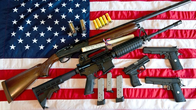 A photo illustration showing a Remington 20-gauge semi-automatic shotgun, a Colt AR-15 semi-automatic rifle, a Colt .45 semi-auto handgun, a Walther PK380 semi-auto handgun and various ammunition clips with a copy of the US Constitution on top of the American flag. (AFP/Getty Images)