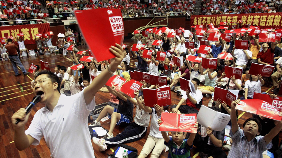 "Li Yang teaches English to several thousand students attending a class at a stadium in Guangzhou, China, in 2004. His ""Crazy English"" technique — based on learning through shouting — draws huge crowds. In interviews, he has admitted physically attacking his wife. (Reuters/Landov)"