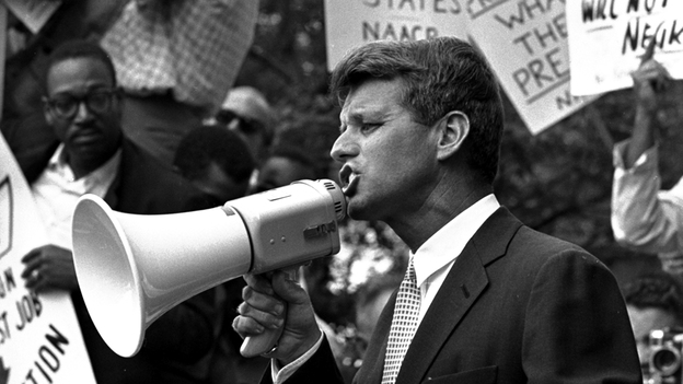 "Attorney General Robert F. ""Bobby"" Kennedy uses a bullhorn to address a crowd of demonstrators, June 14, 1963, at the Justice Department. Four months earlier he had walked 50 miles in one day to prove to his brother John that he could do it. His march helped make extreme walking and hiking popular activities. (AP)"