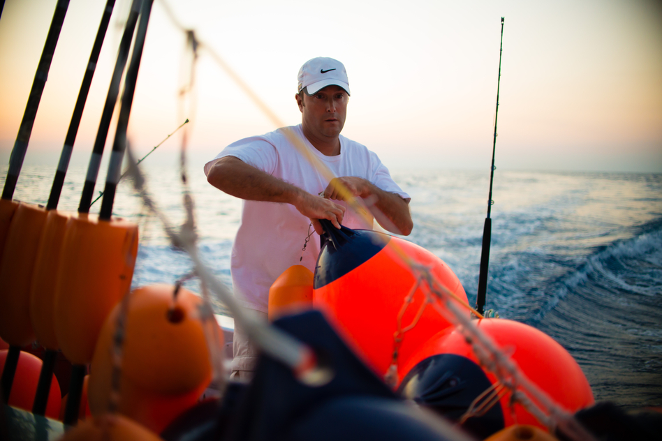 Manganello sets buoys while swordfishing with Palmer. They usually fish with 10-12 buoys that stretch for a mile or two, which have to be repeatedly checked throughout the night for bites. (Chip Litherland for NPR)