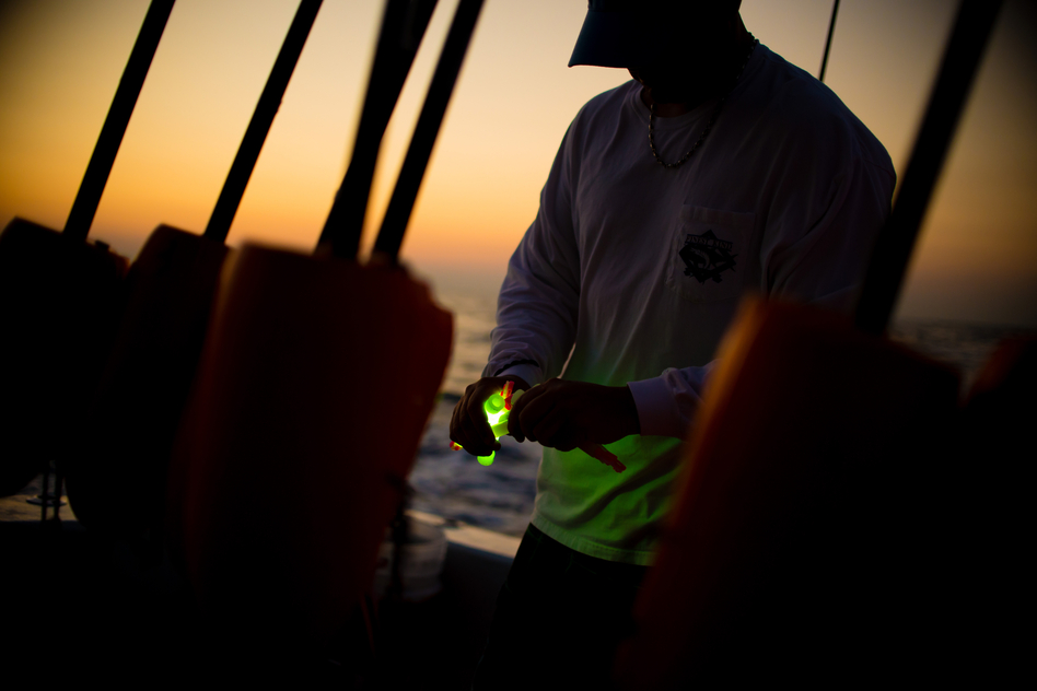 Glow sticks are cracked to be tied to fishing lines. (Chip Litherland for NPR)