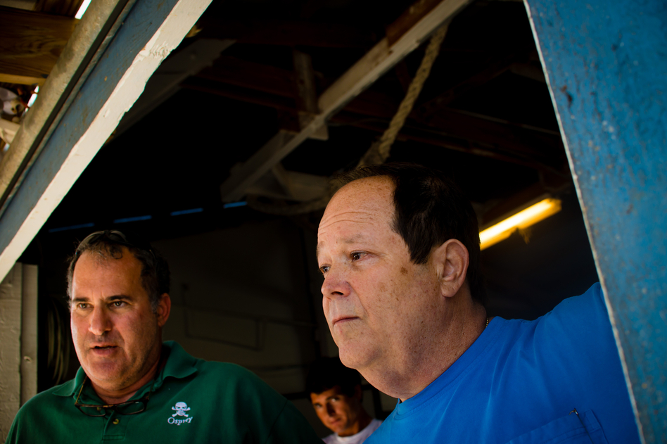 Day Boat Seafood co-owners Scott Taylor (left) and Howard Bubis watch workers unload thousands of pounds of catch from a long-line boat that was out for 10 days at their boathouse in Fort Pierce, Fla. (Chip Litherland for NPR)