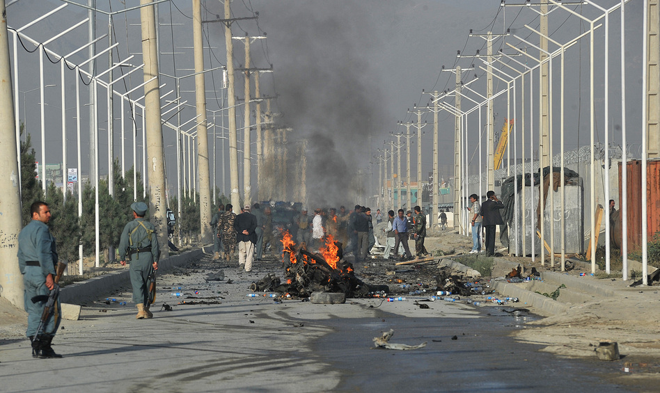 Afghan police and officials visit the site of a suicide attack in Kabul in September. A suicide bomber blew himself up alongside a minivan carrying foreigners on a major highway leading to the international airport in the Afghan capital, police said, killing at least 10 people, including nine foreigners.